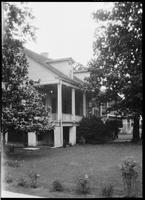 Two-story house with columns and brick chimney: corner view