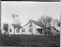 Single story stone and wood house showing a windmill and barn