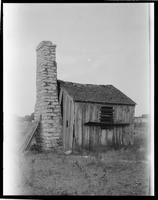 Small wooden shack with exterior stone chimney