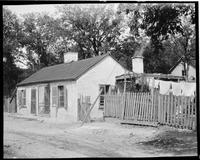 Single story house with paneled roof, covered patio, and picket fence