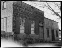 Two-story stone storefront immediately adjacent to single story storefront